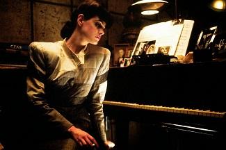"""<img src=""""Rachael"""" alt="""" Rachael ante el piano y las fotografías"""">"""
